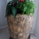 HAND TOOLED WOODEN URN WITH GARDEN PLANTS.